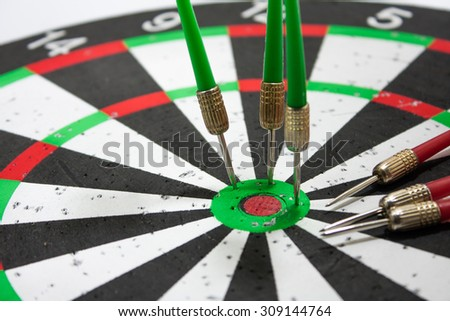 Green darts stuck in a dart board. - stock photo