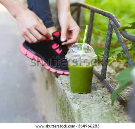 Green detox smoothie cup and woman lacing running shoes before workout. Fitness and healthy lifestyle concept