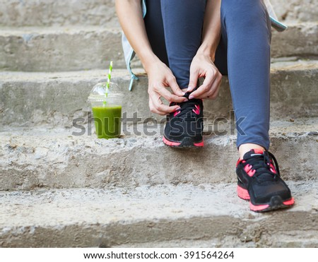 Green detox smoothie cup and woman lacing running shoes before workout. Fitness and healthy lifestyle concept - stock photo
