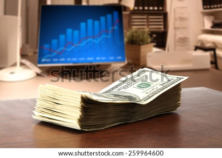 green dollars on brown desk  - stock photo