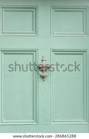 Green Door and knocker conceptual image closeup - stock photo