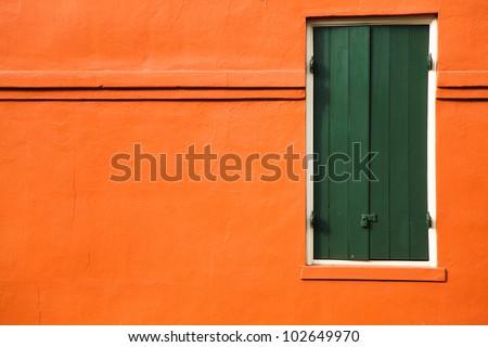 Green door and orange wall - stock photo