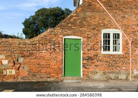 Green door in bricked wall. - stock photo