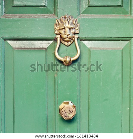 Green door with a brass knocker - stock photo