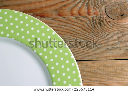 Green dots plate lying on a wooden table - stock photo