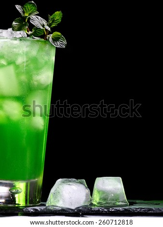Green drink  with crushed ice and mint leaf on dark background. - stock photo