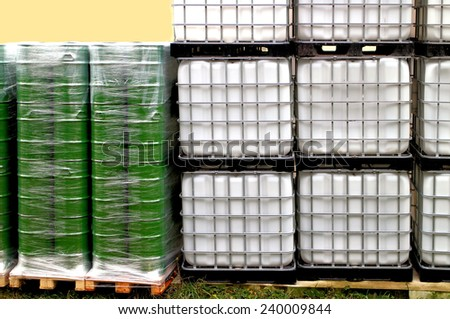 Green drums and white container on a chemical site - stock photo