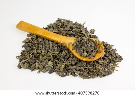 Green dry tea and wooden spoon on white background