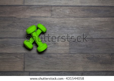 Green dumbbell exercise weights on dark wood background. Top view. - stock photo