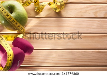 Green dumbbells, apple and tape measure on wooden floor for women. Concept health, diet and sports. Horizontal composition. Top view - stock photo