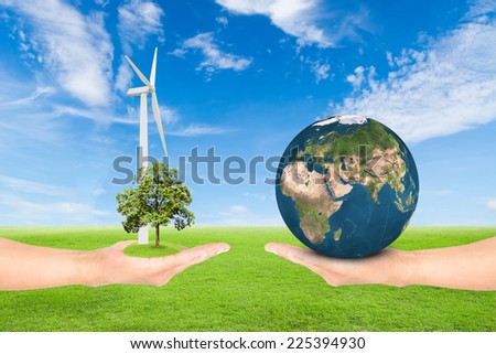 Green Earth concept,hand holding tree with wind turbine and earth against green field and blue sky background. Elements of this image furnished by NASA