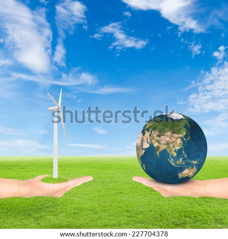Green Earth concept,hand holding wind turbine and earth against green field and blue sky background.Elements of this image furnished by NASA - stock photo