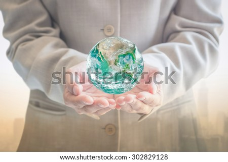 Green earth over businessman's hand (shallow focus) with blurred background of urban office buildings: Saving sustainable economy business concept: Elements of this image furnished by NASA  - stock photo
