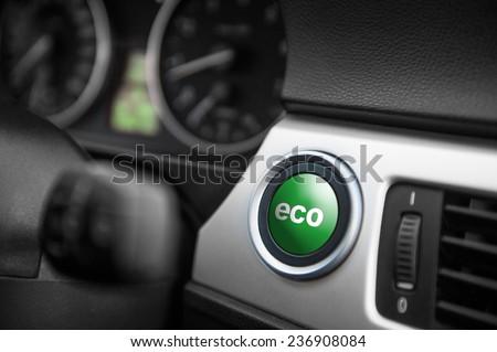 Green ECO button on a dashboard of a sportive car. - stock photo