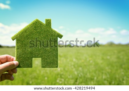 Green eco house environmental background in field for future residential building plot - stock photo