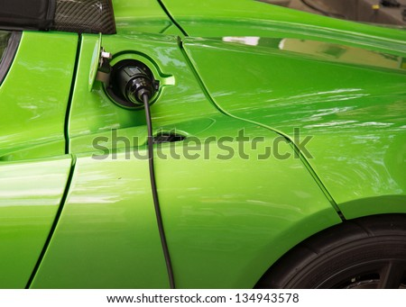 Green electric car charging: Close-up of indistinguishable electric car 'fueling', i.e. plugged to the electricity hose, charging battery. - stock photo