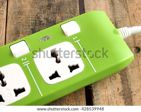 green electric socket on the wood background. Close up. - stock photo