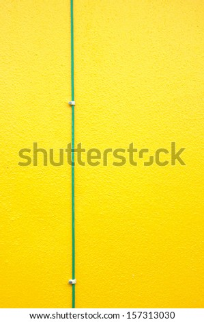 Green electrical ground wire on yellow wall