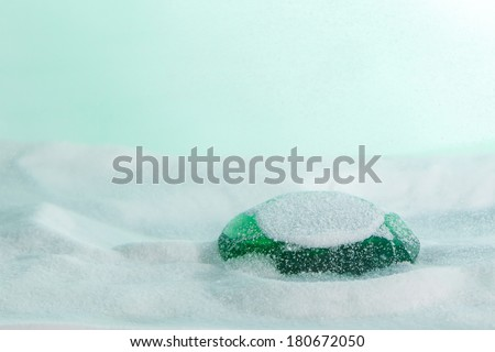 Green emerald sunk through the sandy floor against a light green background - stock photo