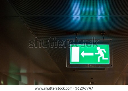 Green emergency exit sign,  hanging from a ceiling. - stock photo