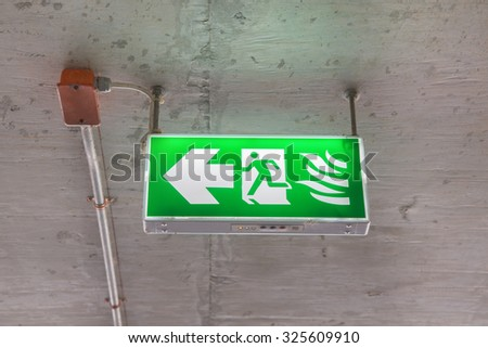 green emergency exit sign in public building - stock photo