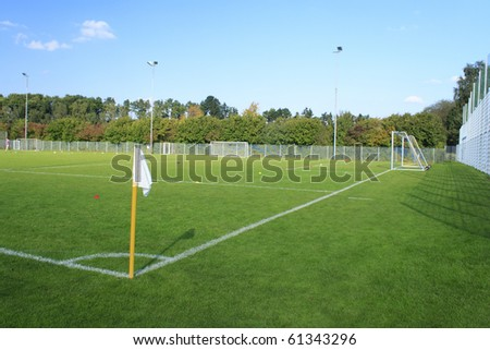 Green empty football field in summer with white flag - stock photo