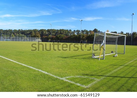 green empty football field with flag and nets - stock photo