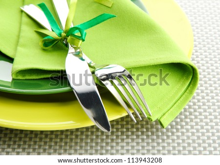 Green empty plates with fork and knife on a grey tablecloth - stock photo
