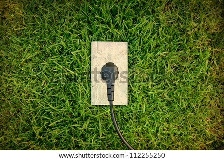 Green energy concept : outlet in grass - stock photo