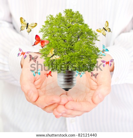 Green energy concept - save green planet. Hands and ecobulb - stock photo
