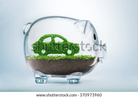 Green energy concept with grass growing in shape of car inside transparent piggy bank - stock photo
