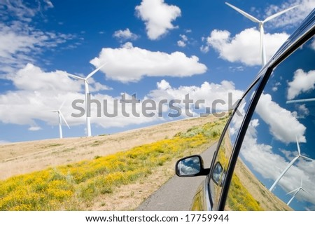 Green energy concept with wind turbines reflected in a car window