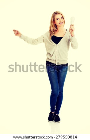 Green energy concept. Woman with led light bulb holding copy space. - stock photo