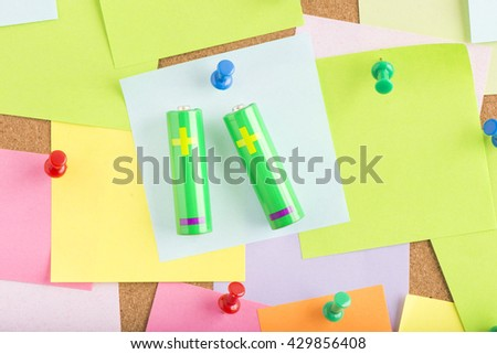Green energy in office, AA batteries as reminder on notice board. Concept image of eco friendly power, electricity and technology. - stock photo