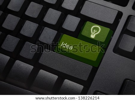 Green energy key with bulb light icon on keyboard - stock photo