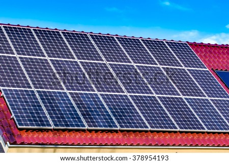 Green energy solar panels on the roof of a house facing the sun making electricity / Green energy solar panels on the roof of a house