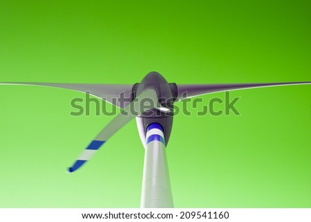 Green energy - Wind turbine in green background - Space on the top for text insertion  - stock photo