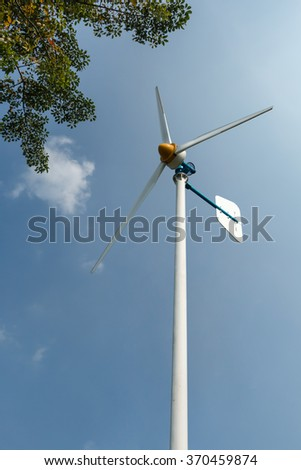 Green Energy Wind Turbine in running on blue sky background.