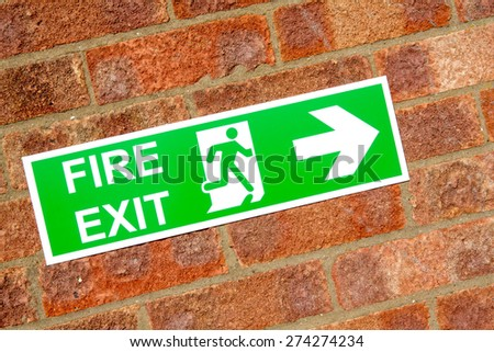 Green exit emergency sign with white lettering on a brick wall background - stock photo
