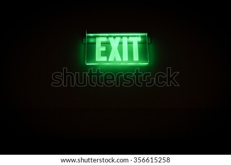 Green Exit Sign Isolated In Dark Black Room   - stock photo