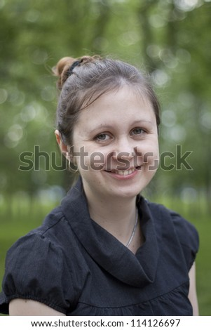 green-eyed girl with dark hair smiling at the park
