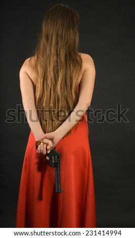 Green-eyed lady in a red dress with a gun - stock photo