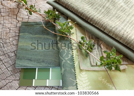 Green fabric swatches with paint color sample cards and a natural stone tile