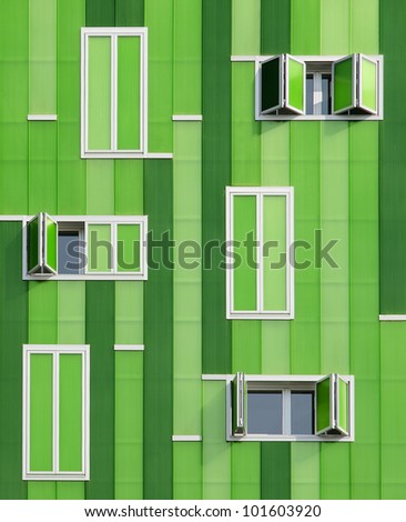 Green facade. Front windows of a green building. Its green facade imitate the texture of bamboo with a lot of parallel vertical lines the windows have different sizes - stock photo