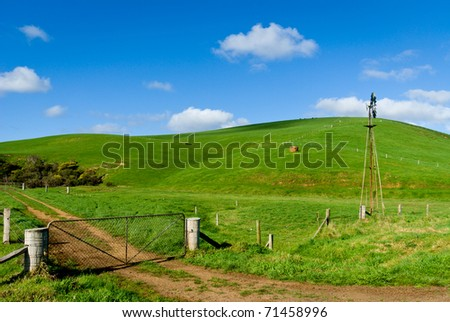 Green farmland with windmill and farm gate in foreground - stock photo