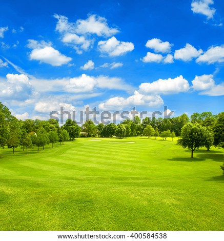 Green field and blue cloudy sky. Golf course. Fairway. European landscape - stock photo