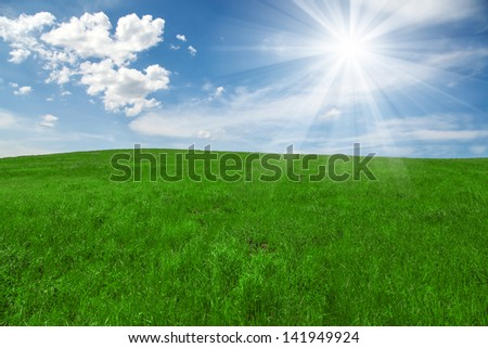 green field and blue cloudy sky with sun - stock photo