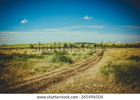 Green field and bright blue perfect sky with clouds. The mountains landscape, The hills in the fog. Morning and day green landscape, horizons. Summer background, road in field  - stock photo