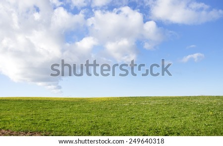 green field and clouds in sky - stock photo
