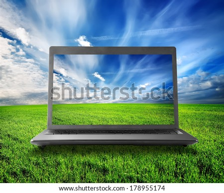 Green field and laptop lit by the sun - stock photo